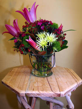 Pink Oriental Lilies, Hypericum berries, Gypsy, green Spider Chrysanthemum, Green Trick Carnations arranged in a glass jar.