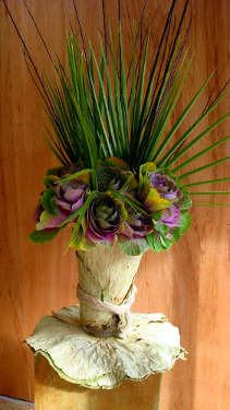 Ornamental kale, black Willow, Fan Palm leaves, and a vase wrapped in Lotus leaves.