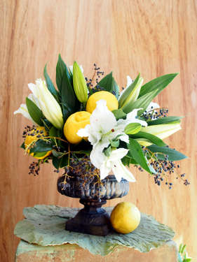 White Oriental lilies and lemons in a cast iron urn. Table centre arrangement