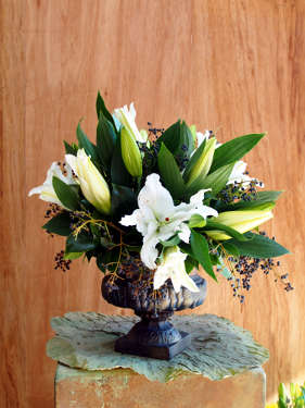 White Oriental lilies and foliage in a cast iron urn. Table centre arrangement